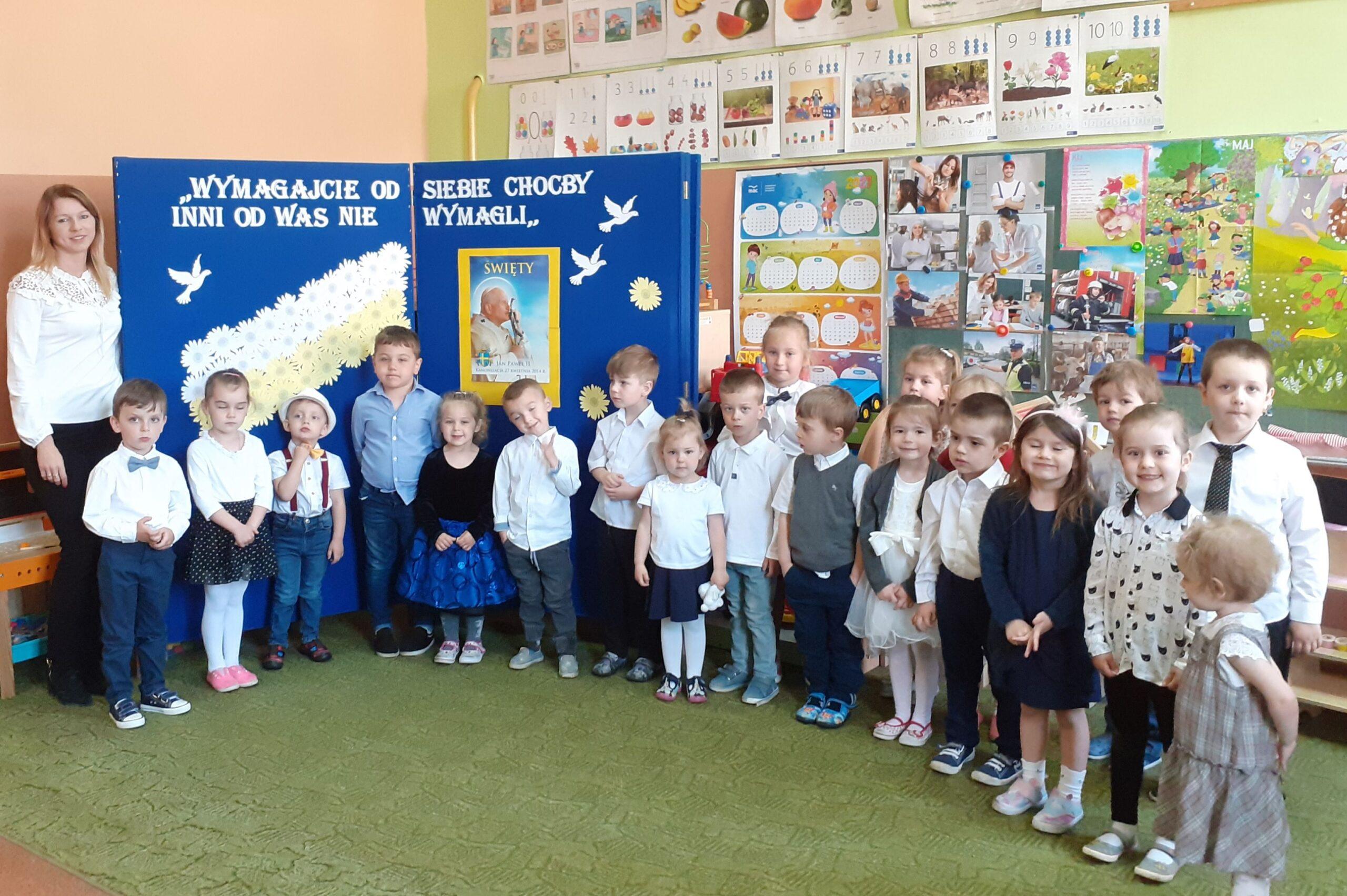 Zdjęcie przedstawia grupę przedszkolaków podczas apelu z okazji 101 rocznicy urodzin Patrona, ubranych w stroje galowe