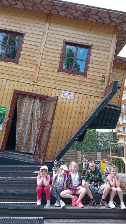 Grupka przedszkolaków na tle domu do góry nogami.