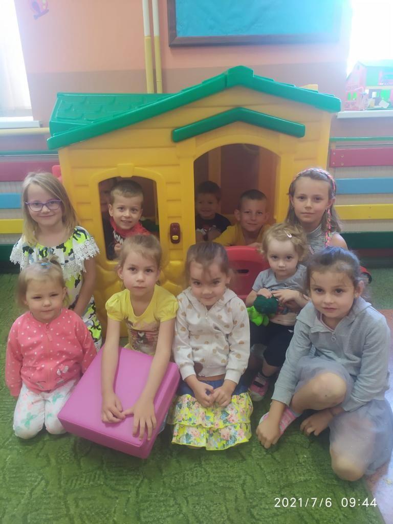 Dzieci przedszkole siedzą na dywanie w sali na tle plastikowego domku do zabawy, niektóre w rękach trzymają siedziska do siedzenia