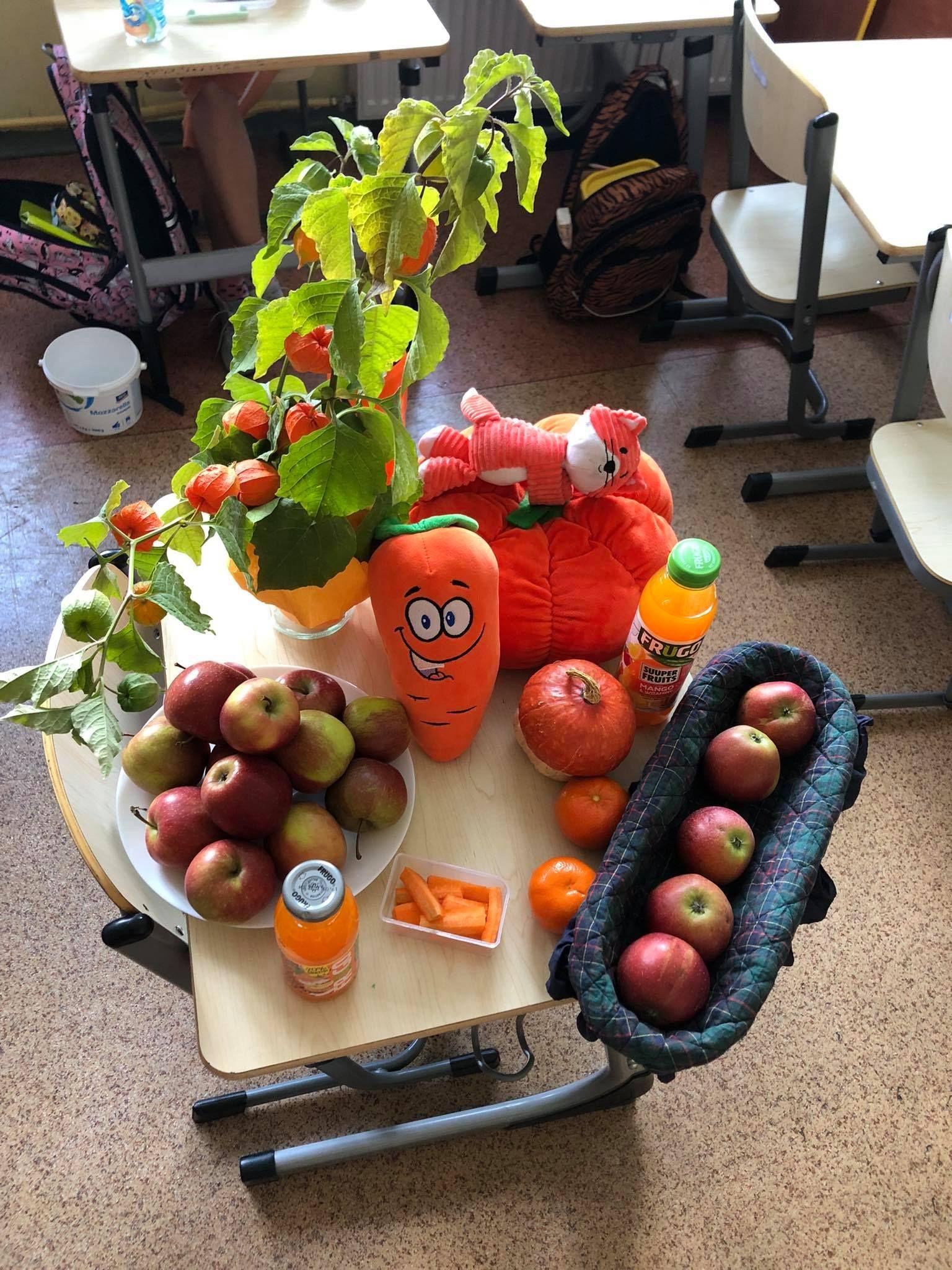 Zdjęcie przedstawia jabłka i i zdrowe produkty w kolorze pomarańczowym ułożone na stoliku.